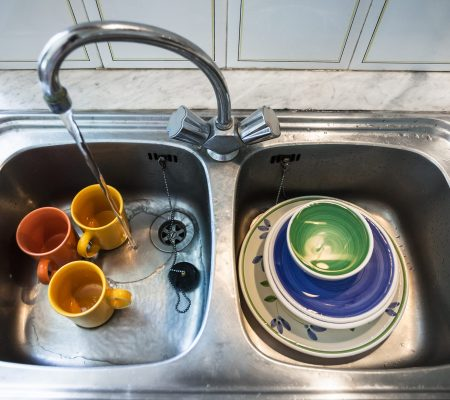Dirty dishes in metallic kitchen sink at home